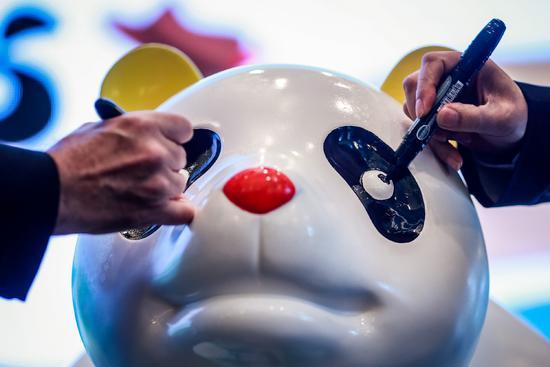 """来宾在启动仪式上为一只熊猫玩偶""""点睛""""。(摄影:新华社记者张帆)"""