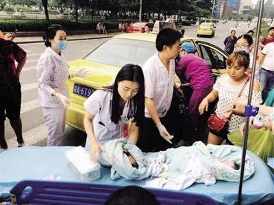产妇租借车上羊水破了,医护职员只能现场助其出产。 本报记者 雷键 通信员 曾理 摄