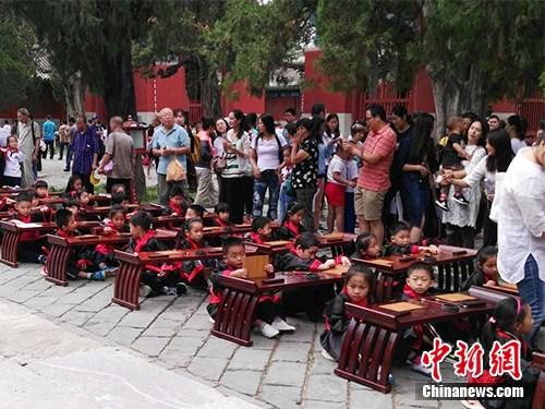 """9月1日,有小学在北京孔庙举办退学""""开笔礼""""典礼,小门生衣着汉服,四周另有家长。中新网记者 宋宇晟 摄"""