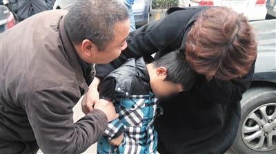 2015年11月12日,8岁男孩遭绑架获救后,家长在一旁安慰他。资料图片/警方供图
