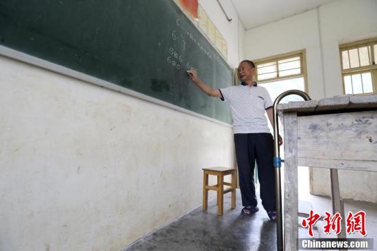 """在广西柳州市融安县东起乡的偏僻山坳里,有一所""""微小学""""――东起乡长丰村小学,2016年秋季学期,这里只有12名学生和一名叫李朝文的老师。李老师年过五十且腿部有残疾,执教38年来,他默默坚守在三尺讲台上,守护着大山里的孩子,被当地人誉为""""最美乡村教师""""。1986年,李朝文老师在学生家访途中腿部摔伤,落下残疾。在腿部受伤后,李朝文拄着拐杖一直坚守在三尺讲台上,至今已经第30个年头。近年来,随着村民外出人数增多,这里上学的孩子也越来越少,老师们也陆续离开,李朝文却一直坚守在这里,独自一人担负起给孩子们教授语文、数学、音乐等6门课程的重任,风雨无阻。他教过的学生,有超过100名学生考上县里或市里的重点高中,有的还考上清华等名牌大学,走出了大山。谭凯兴 摄"""