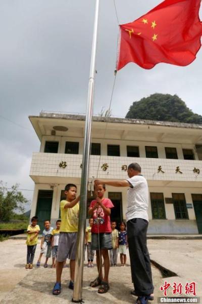 9月9日,在广西柳州市融安县东起乡长丰小学,李朝文教学生们升国旗。谭凯兴 摄