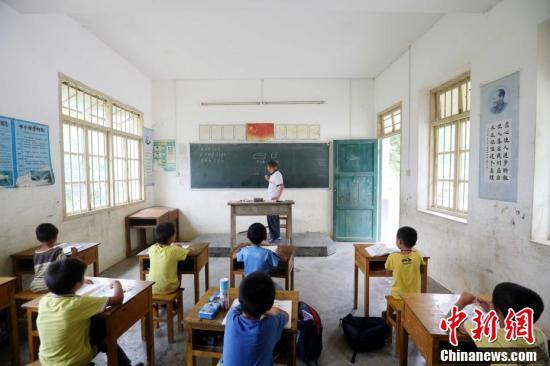 9月9日,在广西柳州市融安县东起乡长丰小学,李朝文在给学生上数学课。谭凯兴 摄