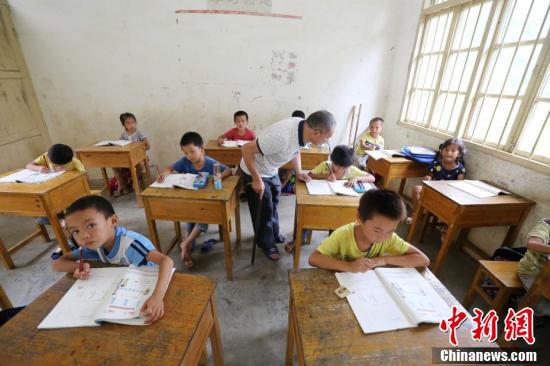 9月9日,在广西柳州市融安县东起乡长丰小学,李朝文在辅导学生们做作业。谭凯兴 摄