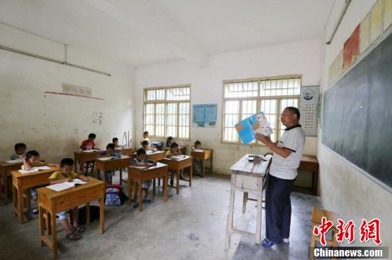9月9日,在广西柳州市融安县东起乡长丰小学,学生们在听李朝文讲课。谭凯兴 摄