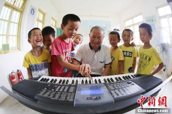 9月9日,在广西柳州市融安县东起乡长丰小学,李朝文在教门生弹电子琴。谭凯兴 摄