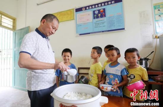 9月9日,在广西柳州市融安县东起乡长丰小学,李朝文在给学生们盛米饭。谭凯兴 摄