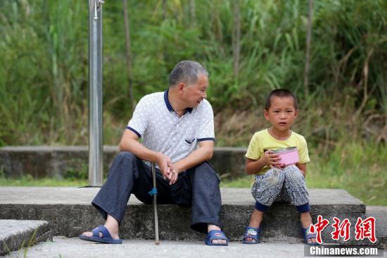 9月9日,在广西柳州市融安县东起乡长丰小学,李朝文在和学生谈心聊天。谭凯兴 摄