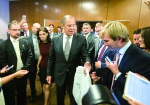 9月9日,在瑞士日内瓦,俄罗斯外长拉夫罗夫(中)向媒体记者赠送伏特加。新华社发