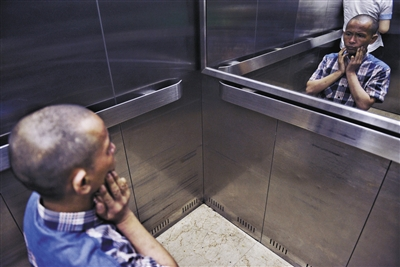 8月29日,浏阳市中医院,彭阳武面对电梯里的镜子观察着自己的脸部出了神。