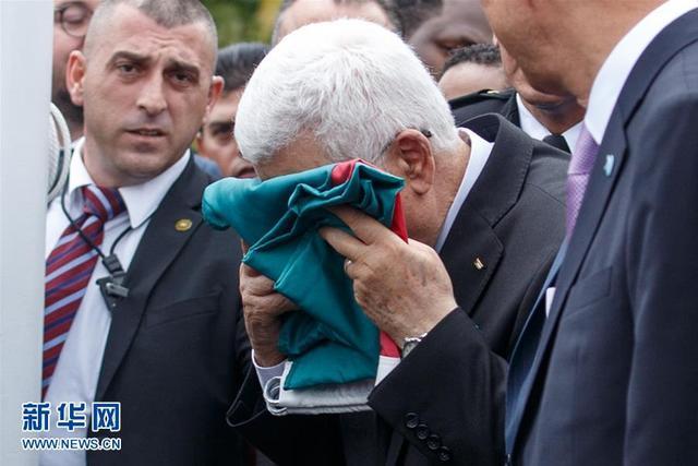 资料图:在纽约联合国总部,巴勒斯坦总统阿巴斯在升旗仪式上亲吻巴勒斯坦国旗。新华社记者李木子摄