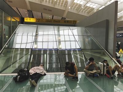 7月下旬,北京南站,旅客在候车大厅席地而坐。