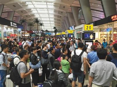 7月下旬,北京南站,旅客在排队候车,背后的候车区域布满商铺。