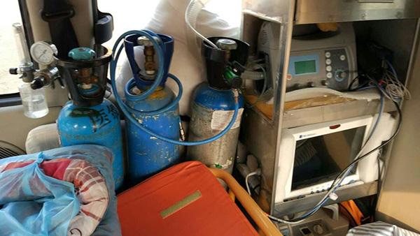 """""""救护车""""靠车窗处摆放着三瓶氧气瓶、心电监控和自动体外除颤仪。"""