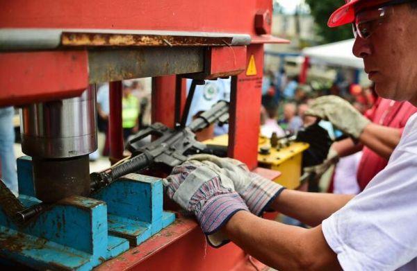 委内瑞拉把警方缴获及民众自动交出的武器,拿去销毁。(法新社)