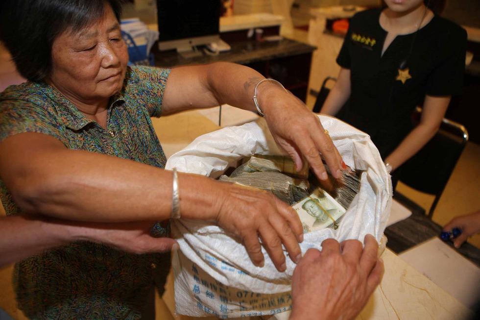 """2016年9月12日,河南南阳,一对老两口背一蛇皮袋零钱,来到南阳市区购买房子。当他们亮出这一袋子""""巨款""""时,售楼小姐惊呆了!"""