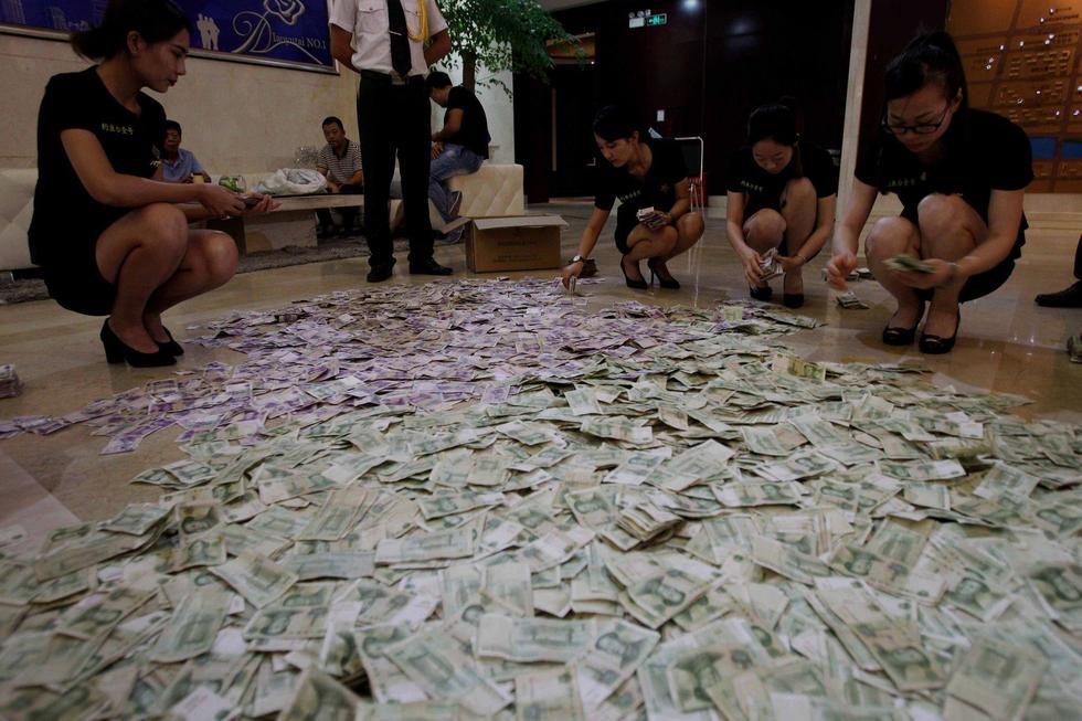 蛇皮袋里装着的大部分都是一元和五元的零钱,大部分纸币褶皱不堪,点钞机难以识别,难坏了售楼处的财务。最后只能抽调多名售楼人员将钱按类别摊开现场数钱。