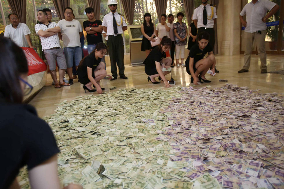 一时间售楼大厅满地都是钱,美女蹲地查钱,安保站岗,场面壮观。
