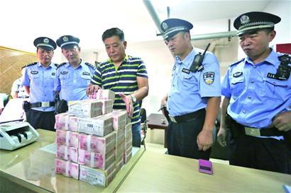 在民警的爱护下,村委干部将现金整顿好,预备发放给乡民。