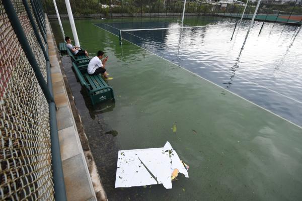 """2016年09月15日,福建省厦门市,两名男生在积水的网球场内""""泡脚""""。 视觉中国 图"""