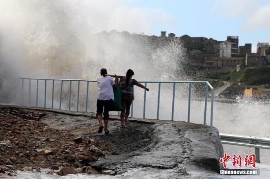 """9月16日,受今年第16号台风马勒卡逼近影响,浙江温岭市石塘镇三岙村海域掀起巨浪,许多观潮者开车蜂拥而来,其中一些观潮者无视潮水威力,瞬间就被巨浪淹没湿身。目前,第16号台风 马勒卡正靠近我国,预计17日给浙江等东部沿海地区带来大风降雨 中新社发 金云国 摄 CNSPHOTO 视频:中央气象台:""""马勒卡""""积蓄能量向东海进发 来源:央视新闻"""