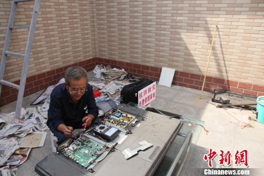 吴和春老人正在为村民修理电器。 张鹏翔 摄