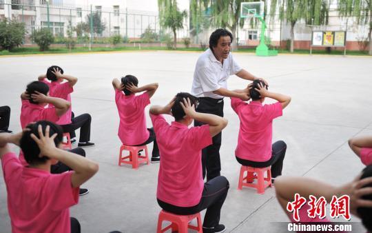 图为甘肃太昊职业培训学校校长、国家级高级中医按摩师莫兴邦指导女子戒毒学员按压穴位。 杨艳敏 摄