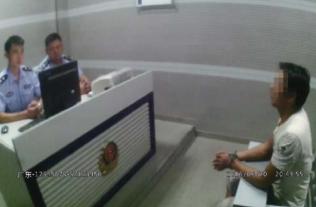 民警正在审讯嫌犯覃某某,视频截图。