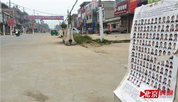 崇礼乡政府门前街道,随处可见通缉令。 图/北京时间
