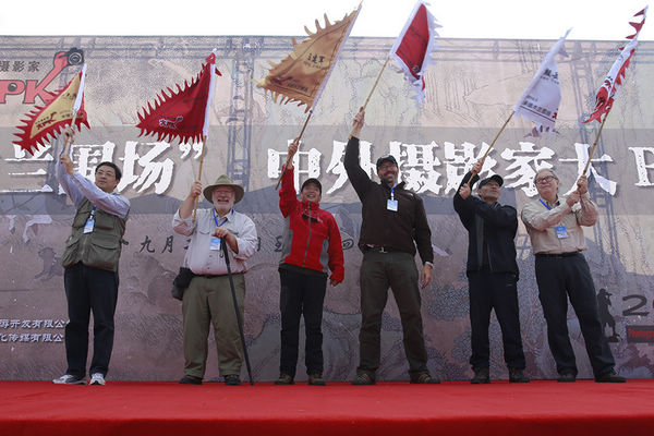 开幕式六位摄影家接受授旗之后挥动手中的PK旗