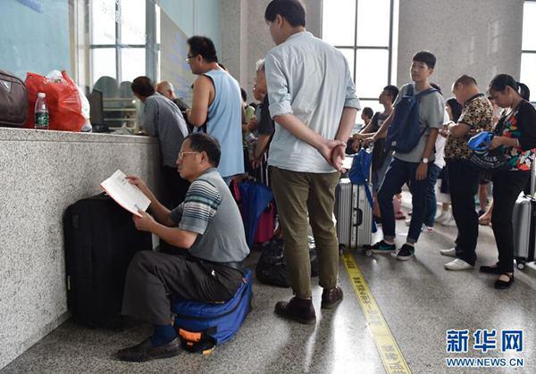 27日,旅客在福州火车站退票改签窗口前排队等候。(图片来源:新华网)