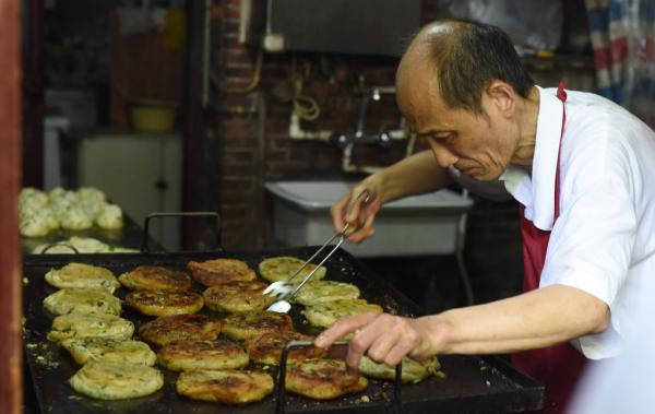 9月26日,上海南昌路,阿大正在做葱油饼。 磅礴新闻记者 张新燕 练习生 刘嘉炜