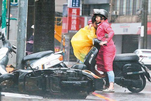 """台中地区9月27日风势强劲,一位骑摩托车的妇人受到""""风阻"""",与亲人紧拥在一起。 台湾《联合报》记者黄仲裕/摄影"""
