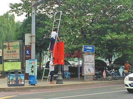 工作人员将国旗取下,准备重新挂正。 丁国彬 图