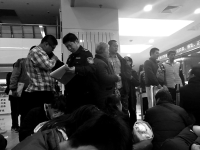 民警对排队挂号者进行登记。
