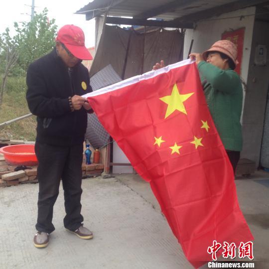 赵伦波老人换了一面新国旗,正在与老伴整理国旗. 刘林 摄-六旬老