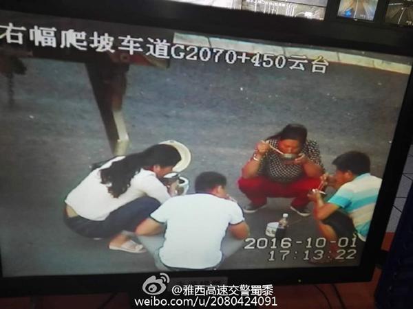 图为两辆货车上下来的四人正在应急车道内吃饭。