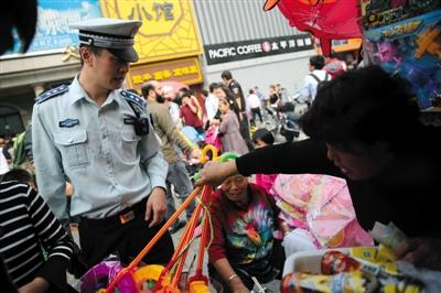 昨日,在北京动物园附近,西城区城管执法部门展览路一队副队长李根在违规经营的书报亭执法。新京报记者 薛�B 摄