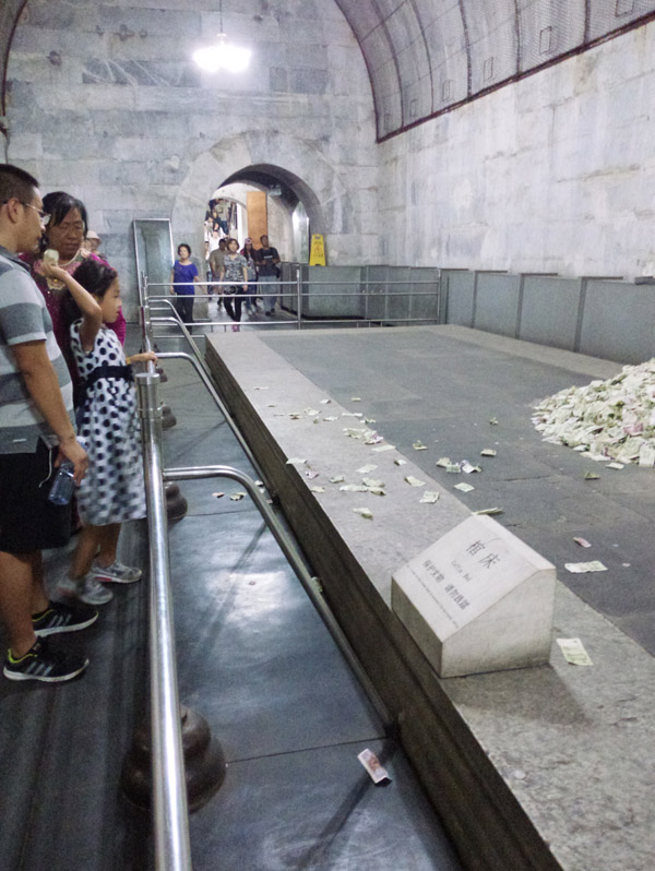 9月16日,定陵景区,游客将钱投向地宫里的棺床。