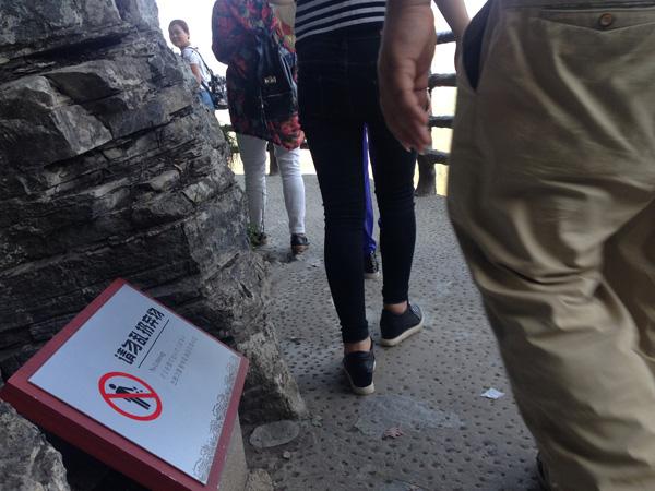 """栈道上虽有""""请勿乱扔弃物""""提示标语,但仍有游客将垃圾抛到悬崖下。"""