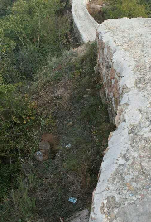 """当地村民准备用水泥桩子和铁丝网,把被""""抹平""""过的这段长城围起来。工程的第一步,是要在长城周围挖出适合栽水泥桩的坑。图为已经挖好的坑。"""