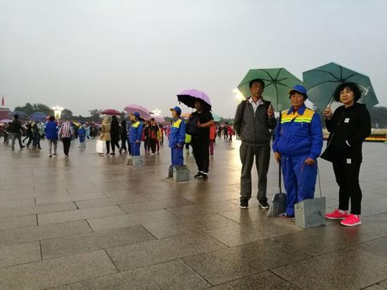 天安门广场游客自发为环卫工打伞