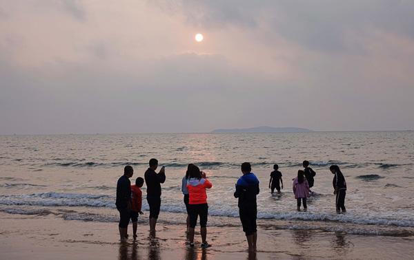2016年10月4日,山东青岛市,游客在金沙滩看日出。 视觉中国 图