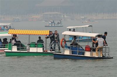 """10月2日,颐和园,两艘游船上的几名男子正在站立嬉戏打闹。在码头的租船游览须知里明确规定""""船上禁止站立、打闹""""。"""