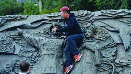 网友拍下游客攀爬沈阳故宫南侧浮雕墙的情景。