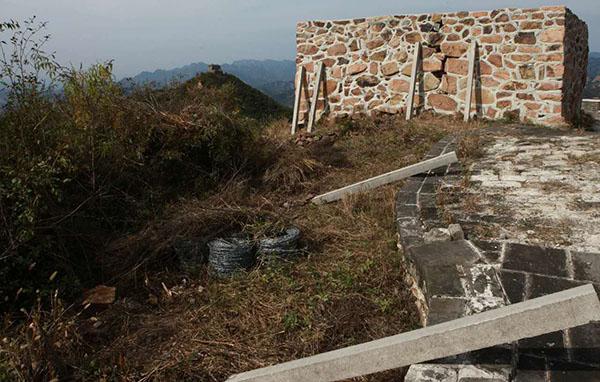 由于物料太多人手不够,当地村民只能把物料分若干小批从长城上往山下运。图为停工现场尚未运走的水泥桩子和铁丝网。 受访者供图