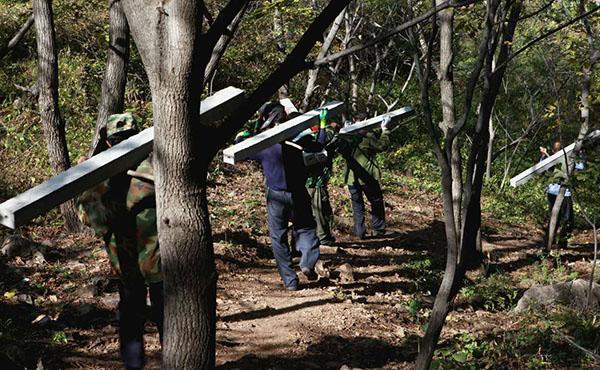 工程停工之后,当地村民正沿着林间小路,把刚运到长城上的水泥桩子运到山下。 受访者供图