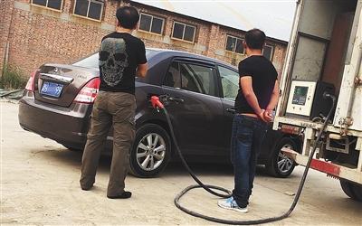 9月26日一早,在精华苑社区西侧一个繁难围挡围成的院内,一辆黑加油车正在给一辆私人车加油。