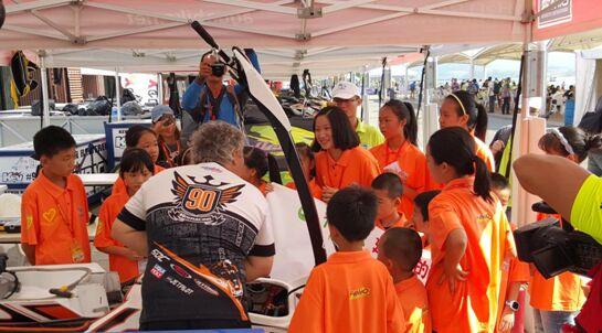 """""""泓燕环保团队""""的同学向机械师请教F1赛艇为什么速度那么快"""