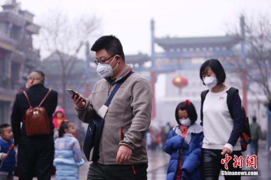 """2016年2月11日,北京开启""""阴雨模式"""",气温有所下降,回暖旋律戛然而止。同时,受不利扩散条件影响,局地空气质量再度降至重度污染水平。图为在北京前门大街游玩的市民。 中新社记者 杜洋 摄"""